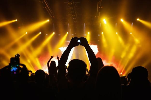 ライトショーの最中に、コンサートステージの前でスマートフォンで写真を撮る