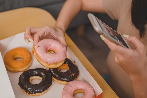소셜 온라인 사이트용 도넛 사진을 찍어보세요. 패스트 푸드 배달 및 집으로 테이크 아웃. 테이크아웃 및 배달 시 도넛을 먹습니다. 거실에서 아시아 여성의 라이프 스타일입니다.