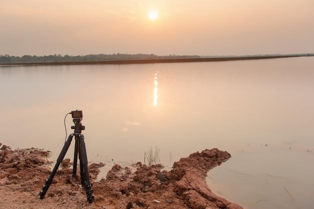 三脚のアクションカメラで川に沈む夕日を撮る