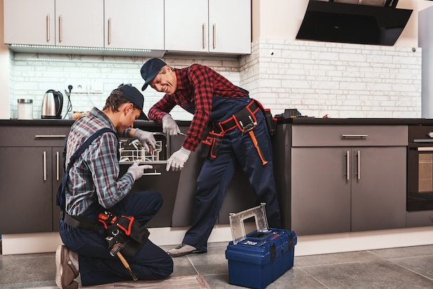 Take a pleasure from success two men technician sitting near dishwasher
