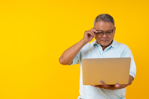 Take on put on glasses. close up portrait of old man looking laptop and touching rim-glassed pop-eyed isolated on yellow copyspace