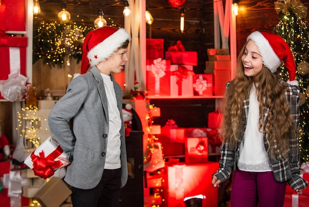 정말 잘 돌봐. 소년과 소녀 산타 클로스 모자입니다. 아이들의 사랑스러운 친구들은 크리스마스 휴가를 만납니다. 조이와 노엘. 가족은 크리스마스를 축하합니다. 공생 개념입니다. 축제 분위기 크리스마스 날입니다.