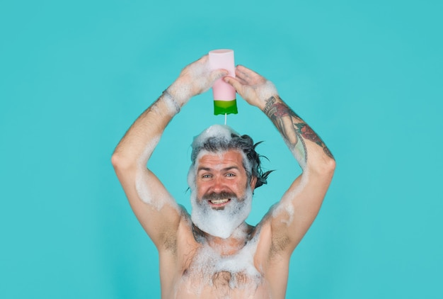 Take a shower man with foam on head mans hair care shampoo bottle conditioner body washing bearded