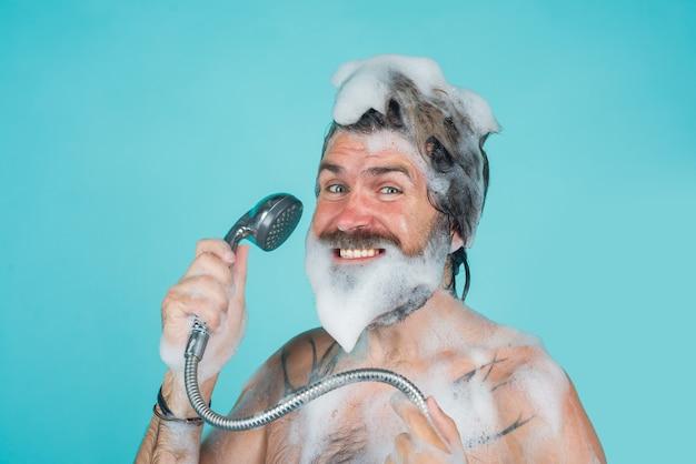 Take a shower man with foam on head shampoo body washing bearded man washing hair hair care spa