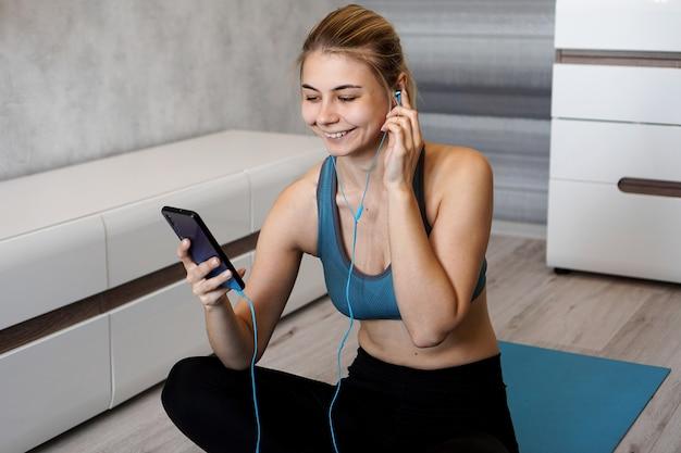 스포츠를 즐기고 음악을 추가하십시오. 음악 재생을 즐기고 바닥에 앉아있는 동안 그녀의 휴대 전화 화면을 터치하는 이어폰으로 여성 운동 선수.