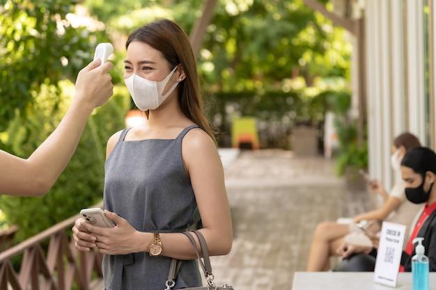 코로나 19 코로나 바이러스 감염증이 발생한 후 새로운 정상으로 소셜 거리 대기열이있는 레스토랑에 들어가기 전에 얼굴 마스크를 착용 한 고객의 온도를 측정하십시오. 레스토랑 뉴 노멀 컨셉.