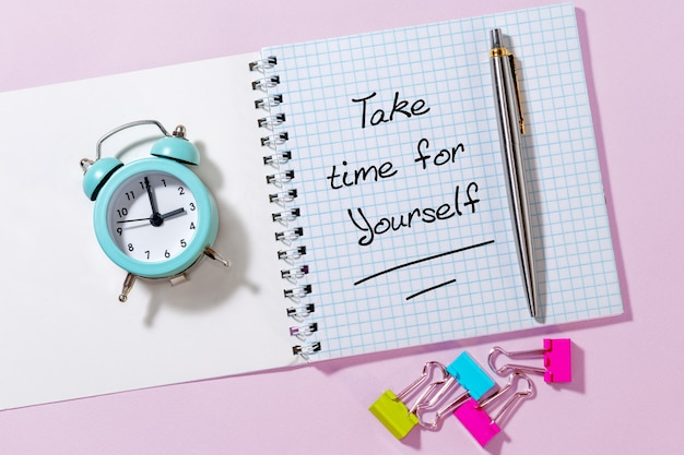 時間をかけてください。明るい背景の動機付けの引用と目覚まし時計。上面図フラットレイコピースペースコンセプト今日の感動的な引用
