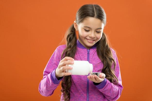 ビタミンサプリメントを服用してください。女の子は薬瓶を持っています。ビタミンと薬の概念。子供の女の子は薬を服用します。ビタミンサプリメントが必要です。健康な消化器系植物のために。子供のための栄養補助食品。