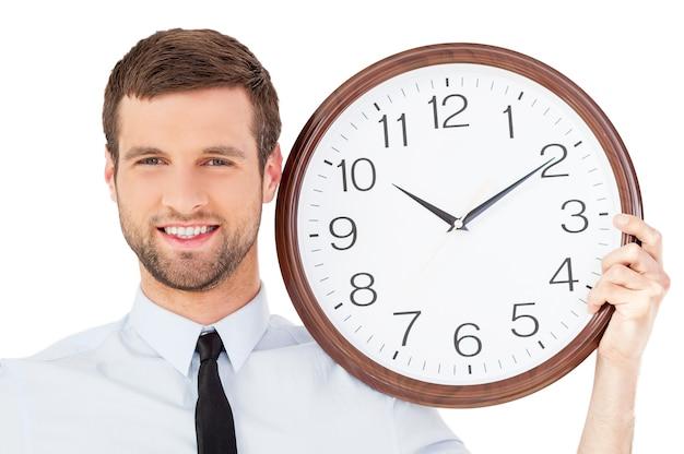 Не торопитесь! красивый молодой человек в формальной одежде держит часы на плече и улыбается, стоя изолированно на белом фоне