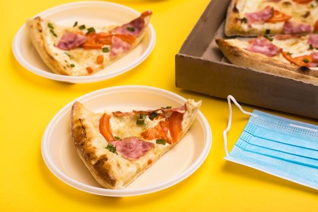Еда на вынос и доставка. кусочек пиццы в одноразовой пластиковой тарелке, коробка пиццы и защитная маска на желтом фоне