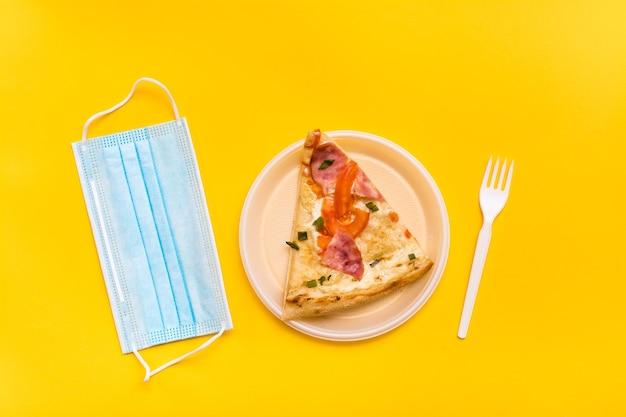 持ち帰りと配達。使い捨てのプラスチックプレートにピザのスライス、保護マスク、黄色の背景にフォーク