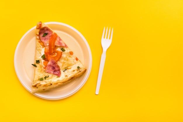 持ち帰りと配達。使い捨てのプラスチックプレートのピザスライスと黄色の背景のフォーク