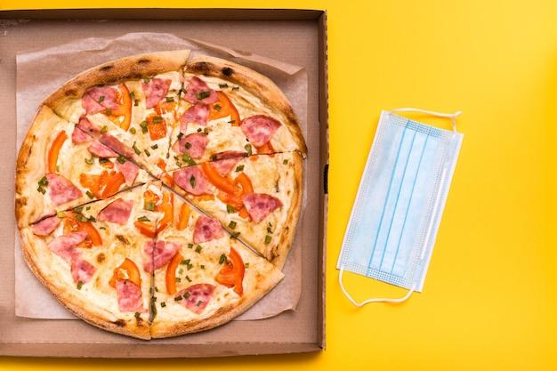 持ち帰りと配達。段ボール箱と黄色の背景に保護マスクですぐに食べられるピザ