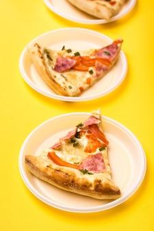持ち帰りと配達。黄色の背景に使い捨てのプラスチックプレートでピザの3つの部分。友達のグループのための昼食。垂直方向のビュー