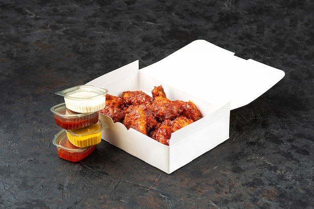 Takeaway box of crispy grilled chicken legs with a spicy marinade served with a hot chili dipping sauce, on a dark stone surface with copyspace.