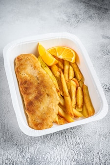 Коробка на вынос блюдо из рыбы с жареным картофелем и картофелем фри. белый фон. вид сверху.