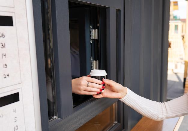 女の子の手に持ち帰り用のコーヒー。仕事を休んで勉強し、外に出てください。