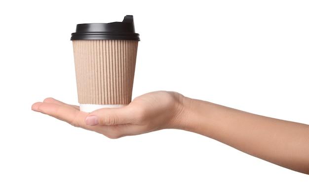 Бумажный стаканчик кофе на вынос на женской ладони изолированной на белой предпосылке.