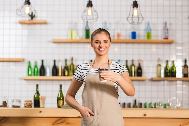 Takeaway coffee. positive cheerful female barista standing in the cafe and smiling while holding a plastic cup with coffee