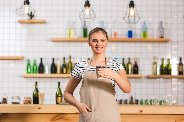 テイクアウトコーヒー。カフェに立って、コーヒーとプラスチックのコップを持って笑っているポジティブで陽気な女性バリスタ