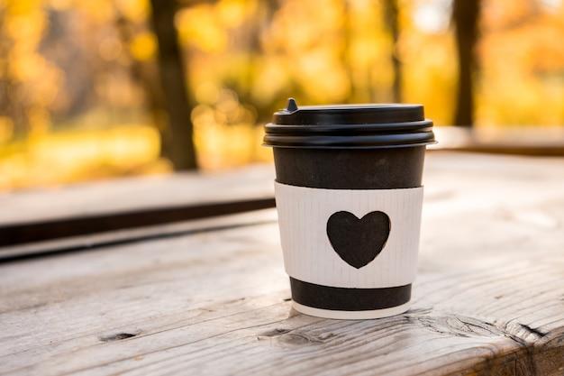 Кофе на вынос с формой сердца на стекле, осенняя концепция. фото высокого качества