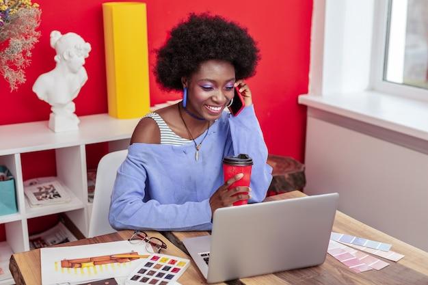 テイクアウトコーヒー。彼女のオフィスで持ち帰り用のコーヒーを飲む若いファッショナブルなインテリアデザイナー