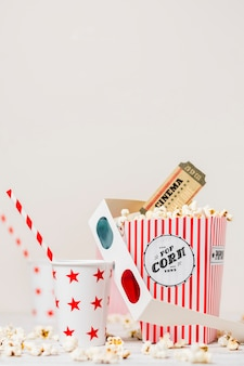 Takeaway drinking glass with straw; 3d glasses; cinema tickets and popcorn box against white backdrop
