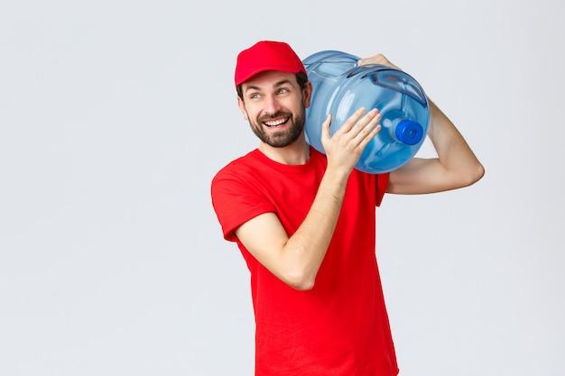 テイクアウト、食品および食料品の配達、covid-19非接触注文のコンセプト。赤い制服を着た陽気な笑顔のひげを生やした宅配便、キャップ、オフィスや家にボトル入りの水を持ってきて、うれしそうに目をそらします