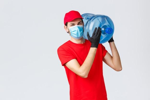 テイクアウト、食品および食料品の配達、covid-19非接触注文のコンセプト。赤い制服を着た若い宅配便、手袋付きのキャップとフェイスマスク、ボトル入り飲料水をオフィスや自宅に届けます