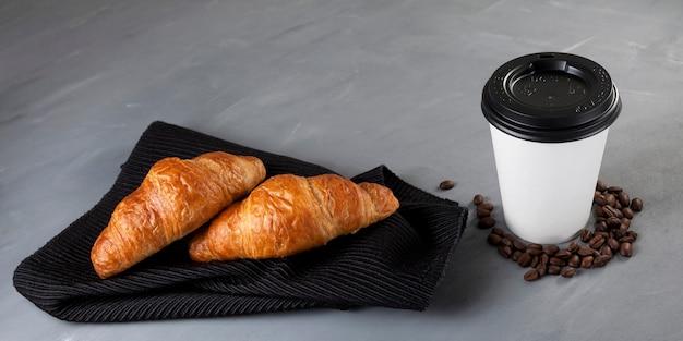 테이크 아웃 음식. 어두운 냅킨에 신선한 크루아상. 근처에는 커피가 담긴 흰 종이컵이 있습니다.