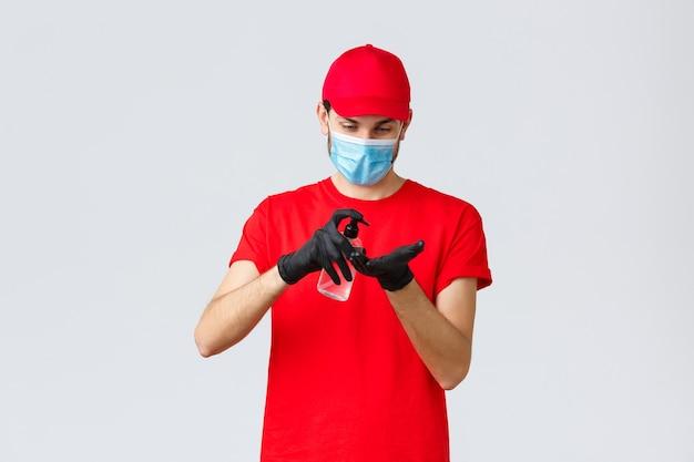Consegna da asporto, cibo e generi alimentari, concetto di ordini contactless covid-19. corriere o dipendente in maglietta rossa e berretto uniforme, indossare maschera facciale e guanti di gomma, applicare disinfettante per le mani