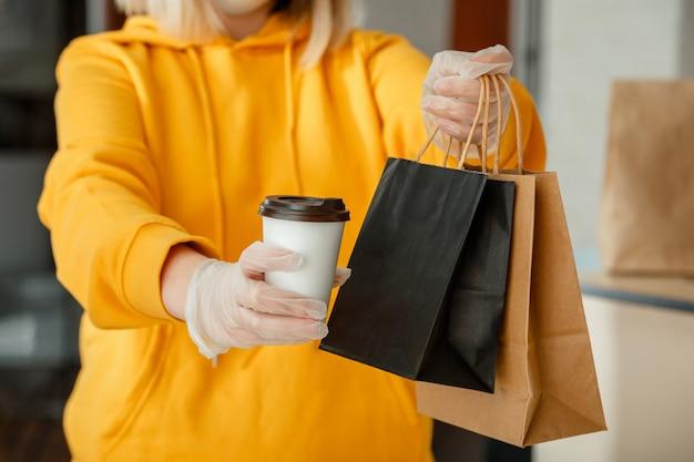 持ち帰り用の食品紙袋、一杯のコーヒーまたは飲み物。テイクアウト レストランで行くフード バッグ ランチ パッケージ。キッチン ワーカーは、手袋をしたままオンライン オーダーを発行します。非接触の食品配達。