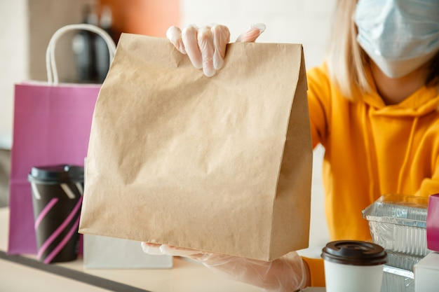 Takeaway food paper bag mock up food bag lunch package to go in takeaway restaurant kitchen worker issues online orders in gloves and mask contactless food delivery during lockdown covid