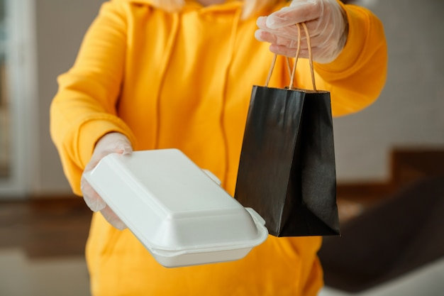 Takeaway food paper bag, styrofoam container. food bag lunch mock up package to go in takeaway restaurant. kitchen worker issues online orders in gloves. contactless food delivery.