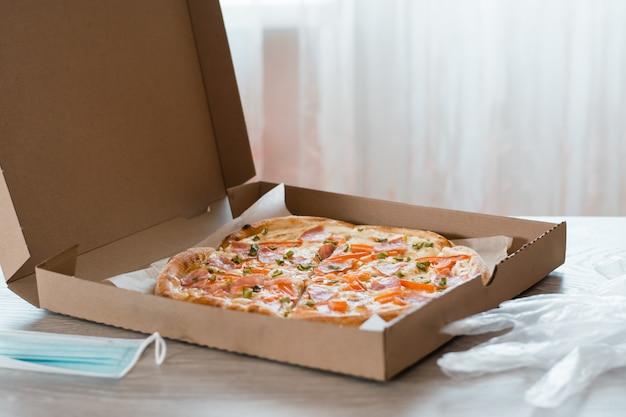 テイクアウト食品。段ボール箱に入ったピザ、手袋、キッチンのテーブルにある保護マスク。
