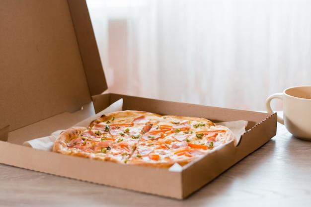 テイクアウト食品。キッチンのテーブルの上の段ボール箱のピザ。
