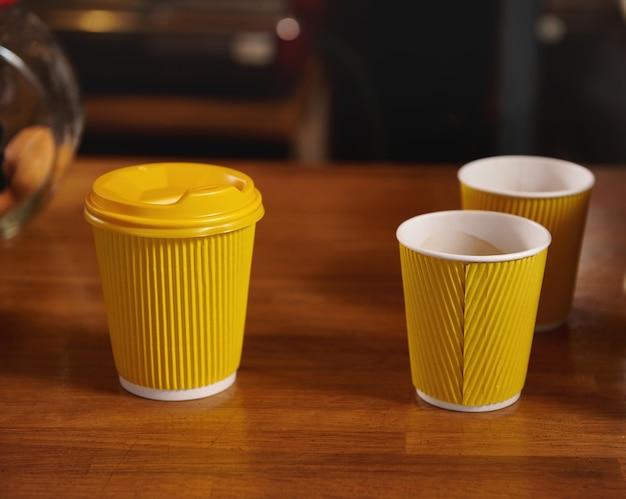 カフェの木製の表面にホットコーヒーとテイクアウトの紙コップ