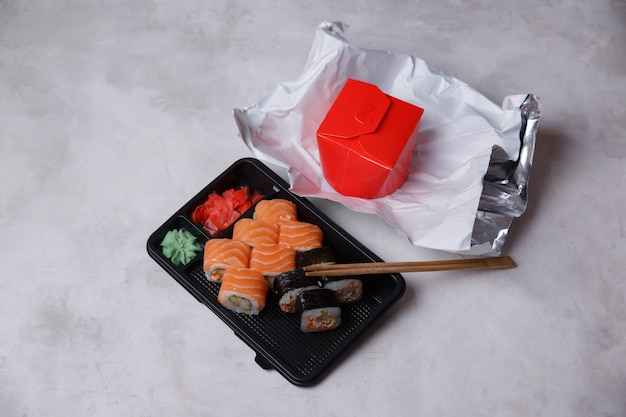 Takeaway rolls in plastic containers, assorted rolls, noodles in a box, soy sauce, pink ginger, wasabi, sushi delivery concept. food ordering