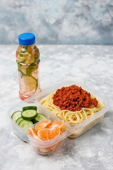 Takeaway spaghetti bolognaise in a plastic lunch box with detox drink and fruit slice on light