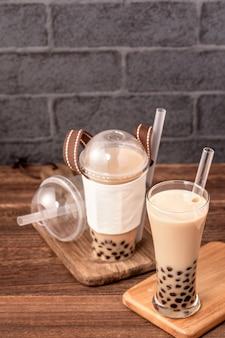 Еда на вынос с концепцией одноразового предмета популярный тайваньский напиток пузырьковый чай с молоком с пластиковой чашкой и соломкой на фоне деревянного стола, крупным планом, копией пространства
