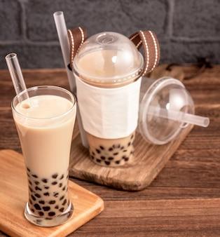 使い捨てアイテムのコンセプトでテイクアウト人気の台湾ドリンクバブルミルクティープラスチックカップと木製のテーブルにストロー