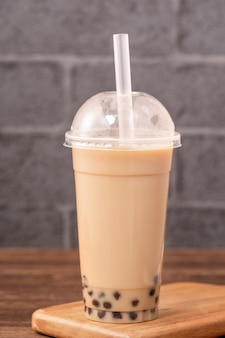 Takeout with disposable item concept popular taiwan drink bubble milk tea with plastic cup and straw on wooden table Premium Photo