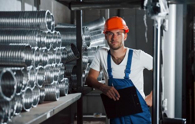 Делает перерыв. мужчина в военной форме работает на производстве. современные промышленные технологии.
