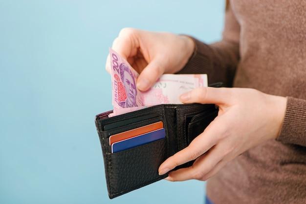 青い背景の財布からウクライナグリブナのお金を取り出します。支払いの概念。