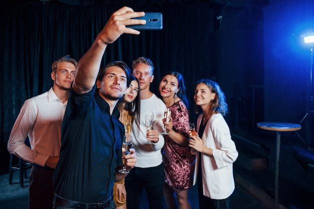 Takes selfie. group of cheerful friends celebrating new year indoors with drinks in hands.