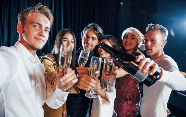 自撮り写真を撮ります。飲み物を片手に屋内で新年を祝う陽気な友人のグループ。