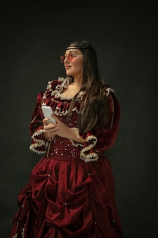 Takes selfie wearing modern eyewear. medieval young woman in red vintage clothing on dark background.