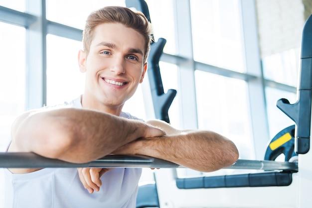 トレーニング後に休憩を取る。ベンチプレスに座って腕を組んでカメラを見ているハンサムな若い男