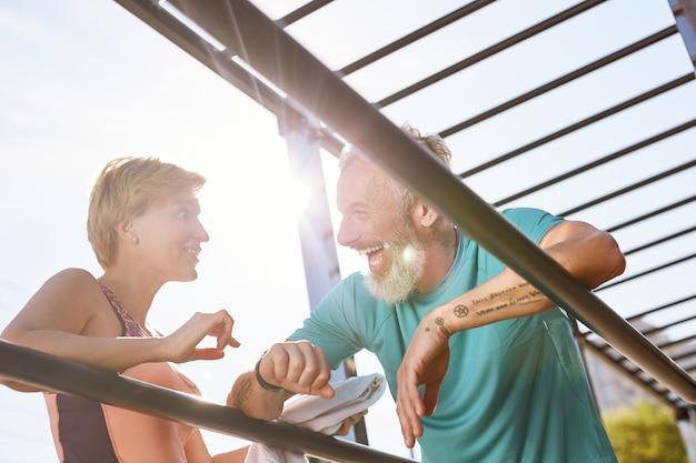 Отдыхая, счастливая спортивная зрелая пара стоит возле брусьев и что-то обсуждает