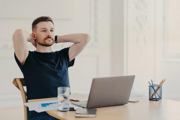 Сделать перерыв. мужчина-фрилансер или предприниматель в расслабленной позе в повседневной одежде смотрит видео или читает информацию на портативном компьютере, работая из дома или в современном офисе